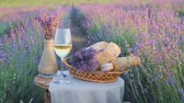 Glass of wine on the canvas cloth. White vase with flowers against lavender landscape in sunset rays. Sunset over a violet lavender field in Provence, France.