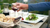 Carafe of red wine with two glasses on the table with dinner dishes. Man reaches for a glass of red wine and takes it.