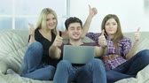 casual : Guy and two girls show thumbs top friends. Happy friends have fun together. Cheerful young people sitting on the couch. People keep smiling and laughing. Stock Footage