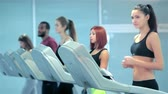 atleta : The treadmill in the gym. Sport and slender girl running on a treadmill. Athlete dressed in sports uniforms and running in the gym.