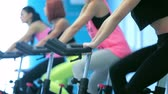atleta : Bicycling to health. Four girlfriends athletes go and pedaled on a stationary bike at the gym