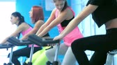 atleta : Training on a bicycles. Athletic girls pedaling on the simulator until her four girlfriends athletes pedaling on a stationary bike at the gym.