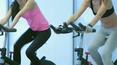 atleta : Fitness classes at the gym. Two young ladies girl pedaling on the simulator look at each other and smiling at the gym.