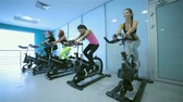 atleta : Group exercises in the gym. Sports friends pedaling and looks in front of a stationary bicycles at the gym. Athletes dressed in sports clothes