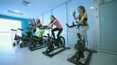 atleta : A great workout. Sport girl pedaling on the simulator and show thumbs up while four friends athletes pedaling on a stationary bike at the gym