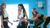 atleta : Healthy sport. Girl athlete receives a call while their friends involved in sports and pedaling on a stationary bike