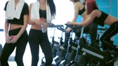 atleta : Great fitness workout in the gym. Girl look at each other and laugh in the gym while their friends do sports and pedaling on a stationary bike
