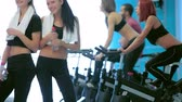 atleta : Great fitness workout in the gym. Girl look at each other and laugh, showing a thumbs up in the gym while their friends do sports and pedaling on a stationary bike
