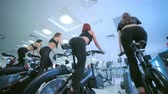 atleta : A group of girls female athletes on a stationary bike. Beautiful sport.