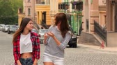 длинношерстный : Visiting a destination city on holiday. Vacation travel. Two young women walking in the city.