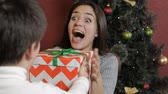 vela : Pretty young woman getting christmas surprise from little boy. Attractive caucasian woman covering her eyes by her hands against background of christmas tree. Brunette woman removing her hands from her eyes to see christmas surprise from her little son