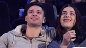 auditório : Close up of attractive young couple laughing at the movie theater. Caucasian girl and her boyfriend watching funny comedy at the cinema. Pretty female viewer tilting her head forward