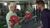 Young male trainer giving barbell to the senior client at the gym. Caucasian bearded guy showing exercise to his ward. Aged man holding barbell in his hands