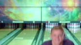 knocking : Young caucasian man showing his thumbs up at the bowling alley. Blond boy taking ball from the floor. Attractive guy knocking down few pins