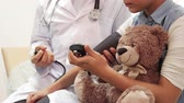 examine : A close-up view of doctor measure the girl s blood pressure. The girl is sitting at doctors appointment. In her hands she holds her soft bear and a stopwatch. Her doctor is sitting next to her Stock Footage