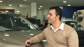 сцепление : The man turns his head and inspects what is inside the car salon. Then his gaze stops on the camera. He smiles and shows a thumbs up Стоковые видеозаписи