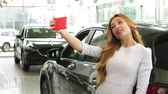 аренда : Young beautiful happy woman smiling cheerfully using her smart phone taking selfies with her newly bough automobile at the dealership customer buyer driver luxury lifestyle Стоковые видеозаписи
