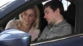 karar vermek : Mature man and his beautiful wife sitting together in a new auto at the dealership examining dashboard and interior comfort lifestyle transport vehicle rental sales retail purchase customers.