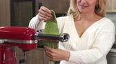 furnished : Cropped close up of a cheerful mature housewife smiling joyfully cooking traditional Italian food at home making homemade pasta on pasta machine dough slicing nutrition healthy. Stock Footage