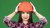 igual : Close up studio shot of a beautiful sexy happy female engineer or constructionist smiling seductively adjusting her hardhat profession femininity confidence feminism equality work employment architect. Stock Footage