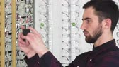 spectacle frame : Profile close up shot of a handsome bearded young man using his smart phone taking photos of glasses on the display while shopping for eyewear at optometrists store consumerism technology.