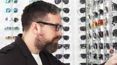 tentar : Close up shot of a bearded mature man smilig cheerfully choosing glasses from the display at the optometrist store consumerism buying eyewear sunglasses protection health retal sales discount.