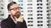 optometria : Close up of a mature bearded male customer looking at the glasses for sale on the display at the eyewear store rubbing his beard thinking consumerism retail purchasing shopping concept.