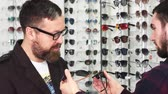 splatnost : Mature bearded man choosing between two pairs of glasses professional optometrist is offering. Young male optician helping his male customer working at the store shopping buying eyewear. Dostupné videozáznamy