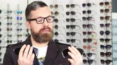 tentação : Bearded male customer choosing between two pairs of sunglasses shopping for eyewear at the optometrists store consumerism buying shopping client purchasing fashion style UV protection.