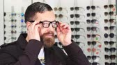tentação : Close up portrait of a happy mature bearded man smiling joyfully putting on glasses showing thumbs up posing at the optometrists store consumerism purchasing buying eyesight.