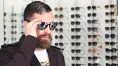 optometria : Close up shot of a bearded mature man trying on new sunglasses at the optometrists store. Handsome male customer choosing new glasses shopping at the eyewear store lifestyle fashion.