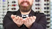 optometria : Cropped close up shot of a cheerful bearded man smiling joyfully holding out glasses to the camera eyesight health vision eyewear optometry concept. Consumerism shopping eyewear.
