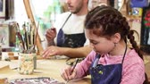 szülői : Little beautiful happy girl enjoying drawing at art studio smiling to the camera her father professional painter artist working on a painting on the background family creativity hobby artistry. Stock mozgókép