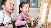 working parents : Cute happy little girl painting a picture on an easel her father watching her. Mature handsome man smiling proudly while his cute little daughter drawing at the art studio painter artist family.