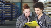 курьер : Two beautiful young female warehouse workers doing paperwork working at the factory. Attractive young woman technician talking with her colleague standing at the storage.