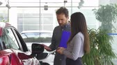 leasing : Professional salesman talking to a young woman at the car dealership salon. Female customer choosing a new automobile at the showroom. Mature auto dealer opening car door for a client.