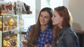 vitrin : Shot of two young beautiful women choosing desserts from the showcase at the bakery store. Female friends shopping for cookies together. Consumerism, buying, sales, purchasing.
