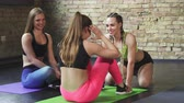 helpful : Beautiful young athletic women working out together at the gym studio. Sportswoman doing sit ups while her friend is helping her. Fitness, toning, muscles, friendship concept.