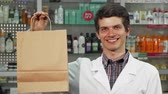 salesperson : Happy handsome young male pharmacist smiling joyfully to the camera, holding a shopping bag. Cheerful clinician working at his drugstore. Consumerism, service, purchase concept.