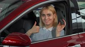leasing : Young beautiful cheerful woman smiling to the camera while sitting in her new automobile. Happy female driver showing thumbs up holding car keys. Transportation, ownership concept.