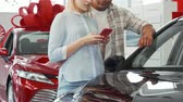 leasing : Cropped shot of a young couple using smart phone at the dealership showroom. Young people choosing new automobile to buy. Consumerism, technology, family vehicle concept. Stock Footage