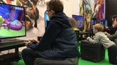 gamers : Brno, Czech Republic - 10112018: Festival Life! Children play XBox games in gaming section. Few little gamers playing on big screens. Teenagers