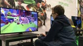gençlik : Brno, Czech Republic - 10102018: Child playing XBox game of life! Young gamer plays on big screens. Teenagers Stok Video