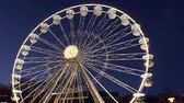 наблюдения : Slow revolving ferris wheel in evening illumination on Christmas street fair in fairground, dark blue sky. Carnival ride on observation wheel at New Year sales. Amusement ride on panoramic wheel