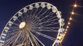 karnawał : Revolving ferris wheel in night illumination on Christmas street fair in fairground, dark blue sky. Bottom shot. Carnival ride on observation wheel at New Year sales. Amusement ride on panoramic wheel