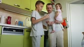перегружены : Fathers day. Cooking father holding small daughter in arms helps son with lessons. Dad making a meal, taking care of small girl and criticizes learning elder boy. 2 children claim parents attention