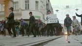gyalogló : Brno, Czech Republic – 01072019: International Silly Walk Day. Fooling walks on banter march. People walking quaint way in street. Funny procession of citizens having fun with up-and-down gait Stock mozgókép