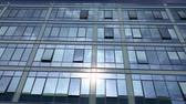 odráží : Business building windows reflecting blue sky, white clouds. Modern architecture in fine weather. Tinted windows in city day on sun light. Reflection in looking glass pattern of construction exterior