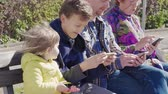 chatování : Modern communication: family with mobile phones outdoor, day. Social network concept. People touching screen, reading on cellphone, typing message, playing game. Man, senior woman, teenage, small girl