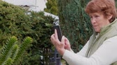 nagymama : Smiling senior woman taking photos, getting selfie by mobile phone in garden, day. Grandmother using smartphone in park. Elder lady taking photo by cellphone outdoor. Active lifestyle of aged, outside Stock mozgókép